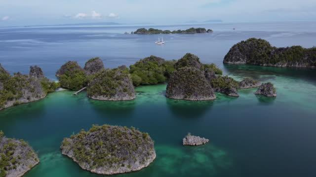 vídeos de stock e filmes b-roll de aerial drone shot of an archipelago and sailboat - arquipélago