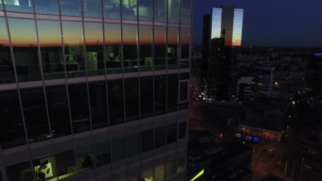 Aerial drone shot of an evening business downtown city landscape with glass buildings. video