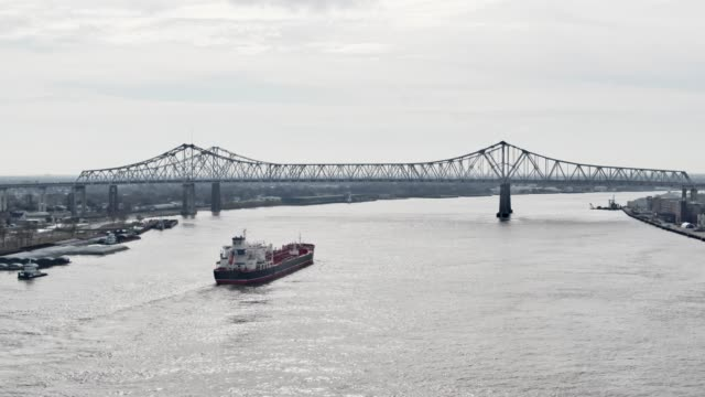 Aerial Drone Shot of Cargo River/Steamboat Sailing Along the Mississippi River toward the Crescent City Connection Bridge next to Downtown New Orleans on an Overcast Day