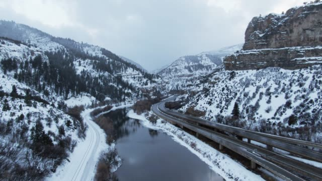 aerial drone shot of cars and vehicles driving on interstate 70 in the rocky mountains of colorado next to the colorado river on a snowy, overcast winter day - колорадо стоковые видео и кадры b-roll