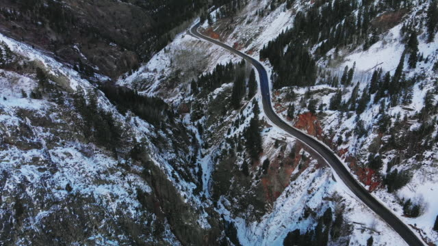 Aerial Drone Shot of Cars Driving Along a Snowy Red Mountain Pass (Road: Million Dollar Highway) in the San Juan Mountains (Rocky Mountain Range) Outside of Ouray, Colorado in Winter Surrounded by a Forest of Trees