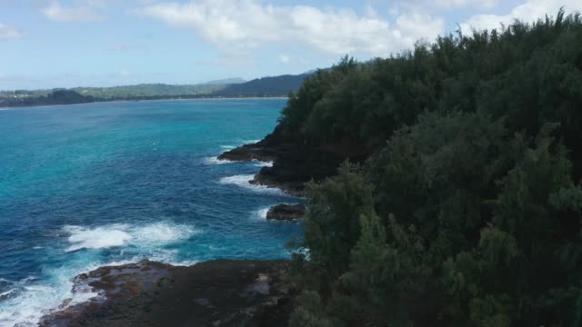 Aerial drone shot of flying away from Lumahai Beach over the rocks on the north shore of Kauai in Hawaii - video