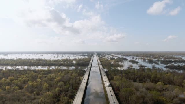vídeos de stock e filmes b-roll de aerial drone shot of flying over breaux bridge (interstate 10) and the atchafalaya river basin swamp surrounded by cypress tree forests in southern louisiana under a sunny but partly cloudy sky - horizonte
