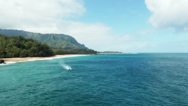 Aerial drone shot of Lumahai Beach with jet ski on the north shore of Kauai in Hawaii - video