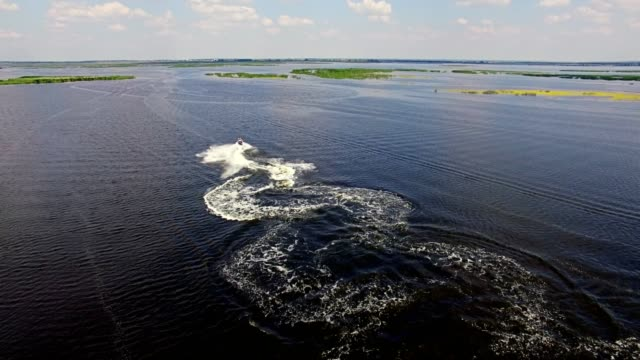 Aerial drone shot of man riding personal water craft on lake