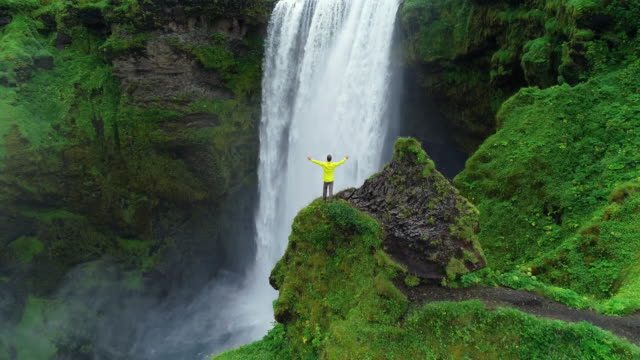 aerial drone shot of man with arms raised on top of cliff standing in front of waterfall celebrating - водопад стоковые видео и кадры b-roll