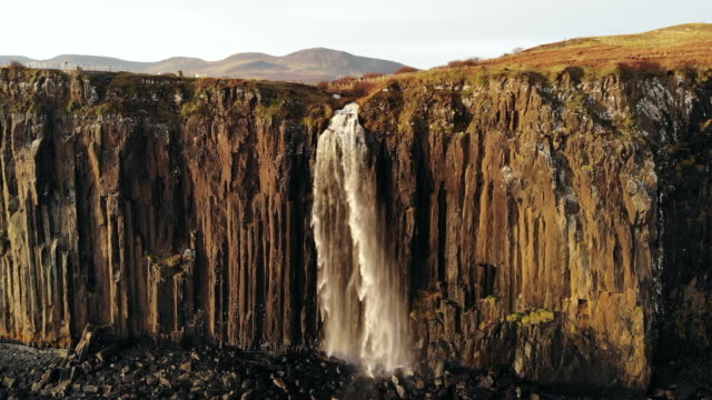 aerial drone shot of mealt falls in scotland isle of skye. waterfall falling into the ocean - highlands scozzesi video stock e b–roll
