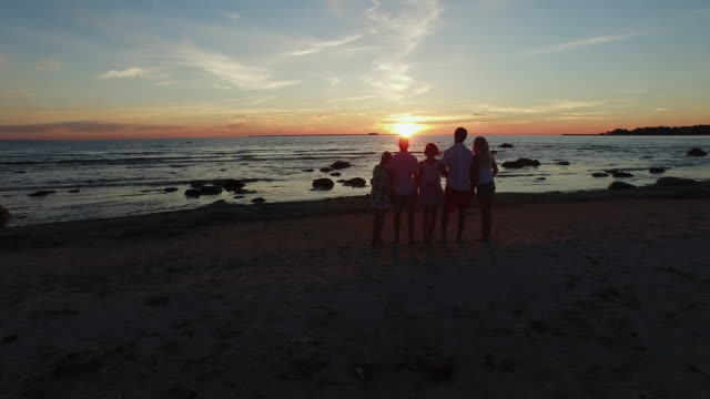 Aerial drone shot of people looking at sunset at the sea coast. video