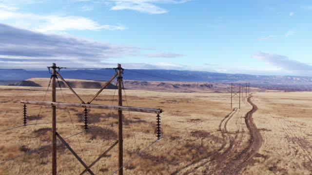 aerial drone shot of power lines above a dirt road and a field of brown grass with the colorado national monument in the background in western colorado under a partly cloudy sky - cavo dell'alta tensione video stock e b–roll
