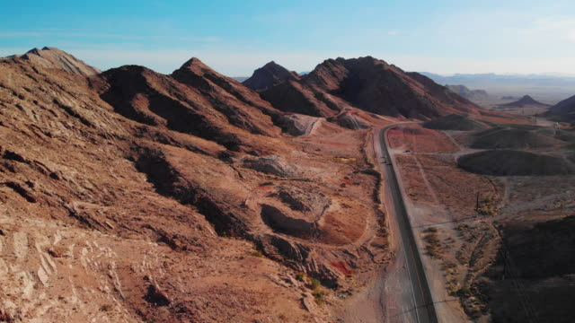 aerial drone shot of red desert mountains next to lake mead road (road leading into and out of las vegas, nevada) - pustynia filmów i materiałów b-roll