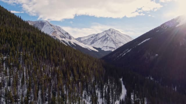 aerial drone shot of snowcapped mountains of the rocky mountains in colorado under a partially cloudy but sunny winter sky - колорадо стоковые видео и кадры b-roll