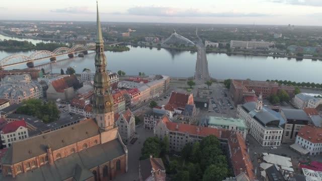 vídeos de stock e filmes b-roll de aerial drone shot of st. peter's church in riga old town - letónia