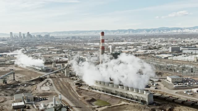 aerial drone shot of steam rising from a power plant in colorado with the rocky mountains and downtown denver in the background on a sunny day - smog video stock e b–roll