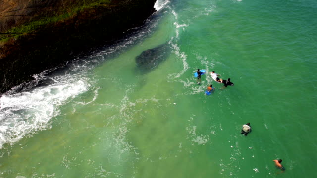 Aerial drone shot of surfers and bodyboarders waiting for wave by rocks in Rio de Janeiro video