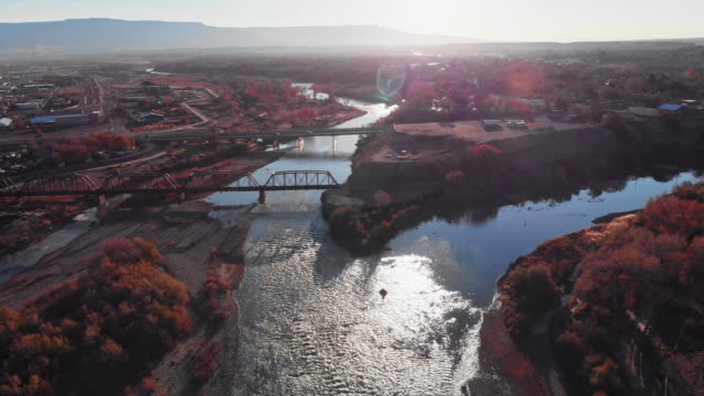 Aerial Drone Shot of the Confluence (Meeting) of the Colorado and Gunnison Rivers in the Middle of the Town of Grand Junction, Colorado in Autumn with Mt. Garfield and the Grand Mesa in the Background