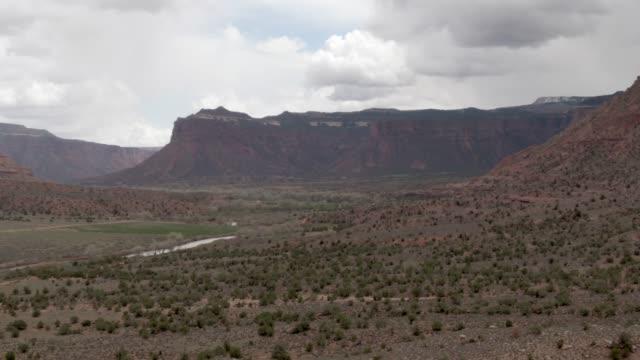 aerial drone shot av high desert cliffs och valley outside gateway i västra colorado under en dramatisk, molnigt himmel - klippiga bergen bildbanksvideor och videomaterial från bakom kulisserna
