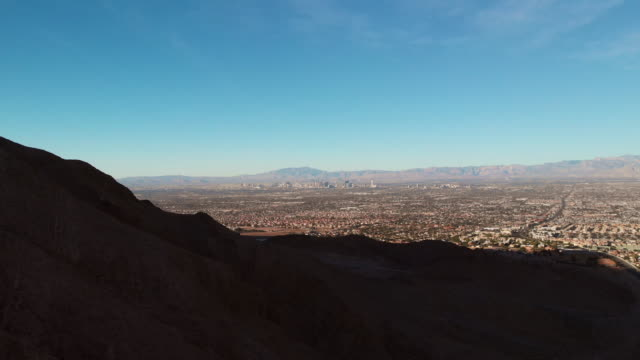 aerial drone shot of the las vegas skyline under a clear, blue sky at sunrise - red rock canyon national conservation area video stock e b–roll