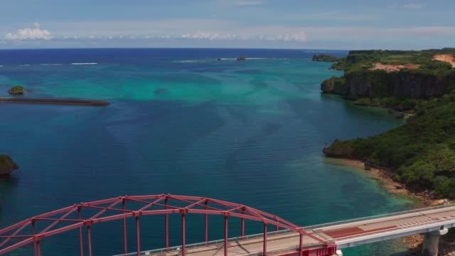 ●赤い宮城橋池井島沖縄日本の空中ドローン撮影。池島サンゴの熱帯海域と海岸線。 - リゾート点の映像素材/bロール