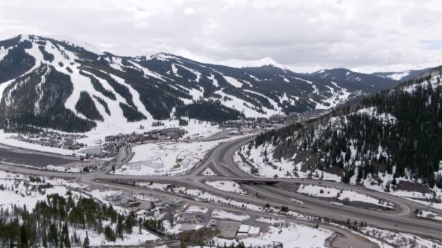 vídeos y material grabado en eventos de stock de avión drone tiro de las pistas de esquí de cobre montaña, colorado en invierno bajo un cielo parcialmente nublado con la interestatal 70 correr a través de él - nieve amontonada