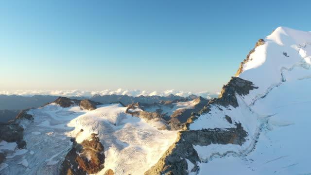 stockvideo's en b-roll-footage met aerial drone shot van de besneeuwde bergen in de buurt van piz palu - sneeuwkap