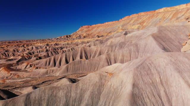 Aerial Drone Shot of the Striped, Eroded Sandstone Cliffs of the Bookcliffs (Geological Formation) and Mt. Garfield in the High Desert of Grand Junction and Palisade, Colorado Against a Vibrant Blue Sky