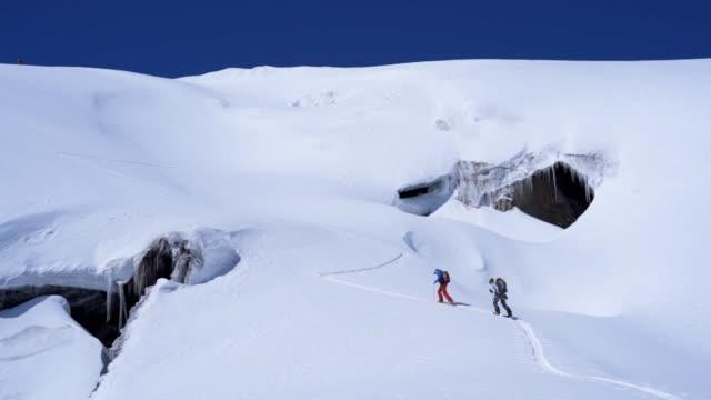 vídeos de stock e filmes b-roll de aerial drone shot of two skiers crossing a snow field in the caucasus mountains - plano picado