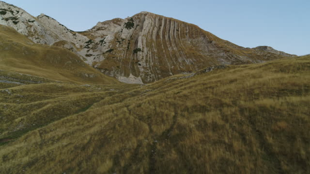 aerial drone shot over grassy hills and mountain with vertical strata in durmitor national park at sunset - эскапизм стоковые видео и кадры b-roll