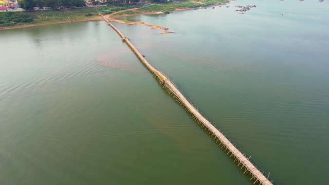 Aerial drone shot revealing a long bamboo bridge connect to the Asian Town