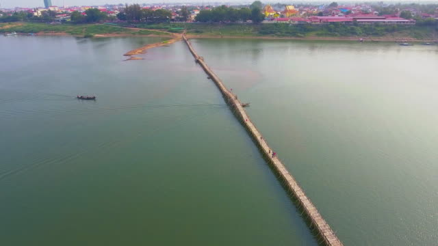 Aerial drone shot : slider shot of a long bamboo bridge over mekong river.
