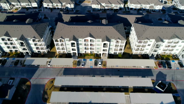 Aerial drone side pan across massive apartment condo buildings in new development Aerial drone side pan across massive apartment condo buildings in new development High up view looking down. house rental stock videos & royalty-free footage