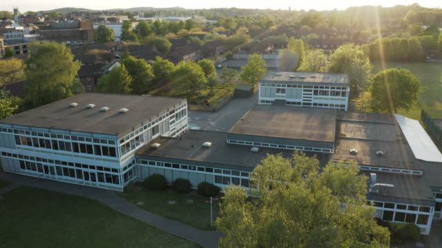 Aerial drone take off outside a generic school building in Hampshire, South of England, UK during summer