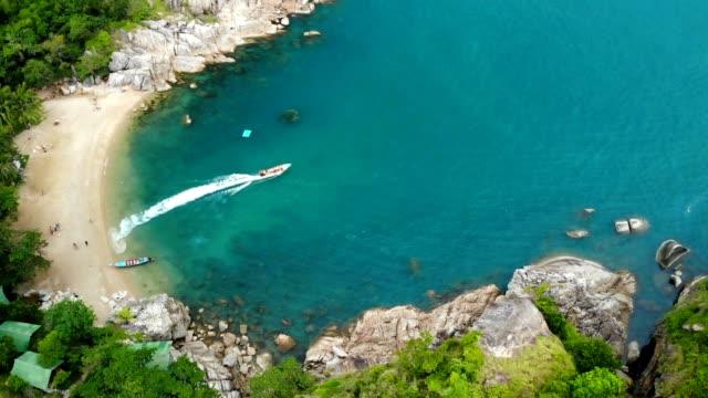 空中ドローン白い砂熱帯のエキゾチックな楽園島 prangan 島、タイで小さな海岸の平面図です。海の表面に小さいボート。火山石と緑のヤシの木のかわいいのリモートのビーチ。 - サムイ島点の映像素材/bロール
