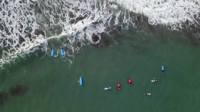 vídeos de stock e filmes b-roll de aerial drone top view over surfers at madeira island ocean wating to surf a wave - ilha da madeira