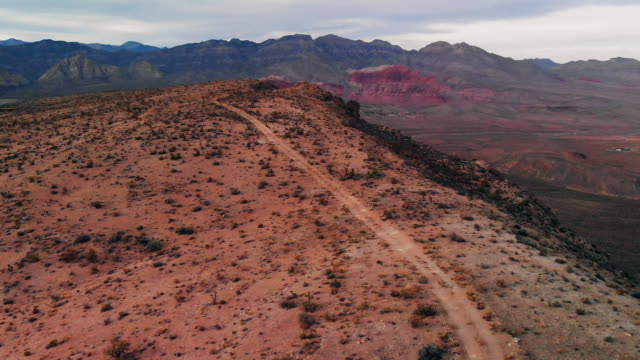 Aerial Drone Trucking Forward Shot of a Dirt Road along a Desert Ridge in Red Rock Canyon National Conservation Shot of Red Rock Canyon National Conservation Area Next to Las Vegas, Nevada at Sunrise/Sunset Under a Cloudy Sky