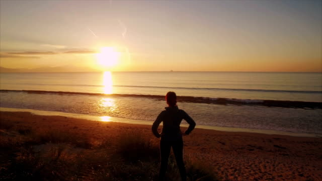 stockvideo's en b-roll-footage met luchtfoto drone video van fit vrouw permanent op strand tijdens zonsondergang - handen op de heupen