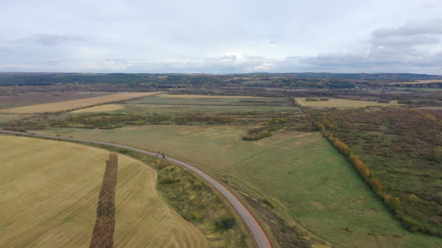 Aerial drone view agriculture crops wheat filed with road and cars. Highway road through field and meadow Landscape. Top View of cars In motion on road. Travel Trip Concept. - video