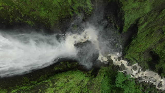 Aerial drone view flying over large waterfall in forest
