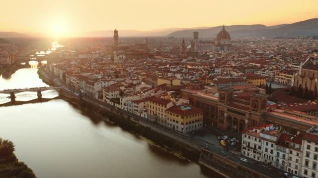 hava drone görünümü: güneşli gününde tarihsel ve kültürel açıdan zengin i̇talyan kasabası. ortaçağ kiliseleri ve katedralleri ile güzel eski şehir. nehir şehir boyunca çalışır - toskana stok videoları ve detay görüntü çekimi
