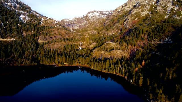 Aerial drone view looking across Amazing Sierra Nevada Mountains at Emerald Bay Sunrise in Lake Tahoe California