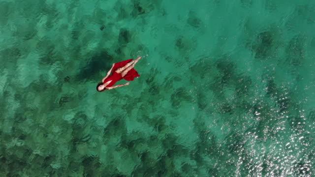 vidéos et rushes de vue aérienne de drone d'une femme flottant et en nageant sur une mer tropicale - mode de la plage