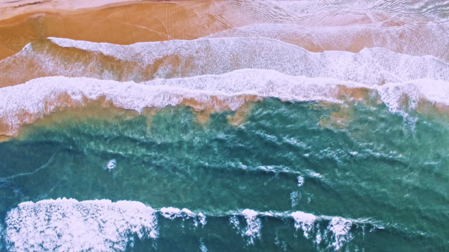 aerial drone view of beautiful waves in turquoise oceans - aerial beach stock videos & royalty-free footage