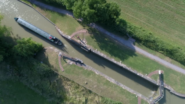 aerial drone view of boat in narrow canal - canale video stock e b–roll
