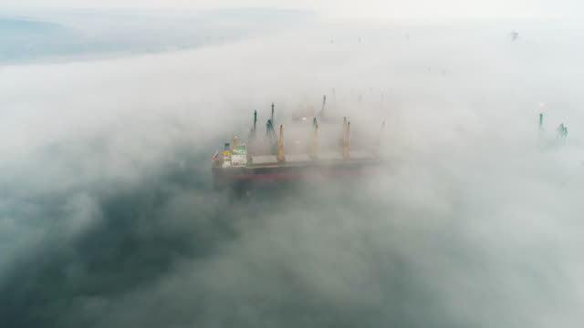 Aerial drone view of cargo ship and industrial cranes in fog in the sea harbor Varna, Bulgaria