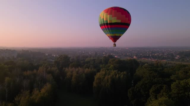 Aerial drone view of colorful air balloon flying over green park and river in small european city at summer sunrise Aerial drone view of colorful air balloon flying over green park and river in small european city at summer sunrise, Kiev region, Ukraine hot air balloon stock videos & royalty-free footage