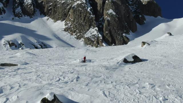 vidéos et rushes de vue aérienne de drone de tour de ski femelle s'élevant vers le haut du paysage alpin enneigé, de hautes montagnes au-dessus - inclinaison vers le haut