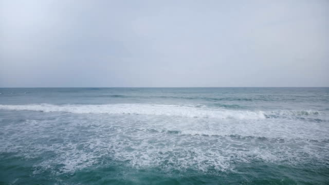 Aerial drone view of foaming waves in beautiful blue open ocean. Breathtaking seascape and cloudy sky horizon panorama
