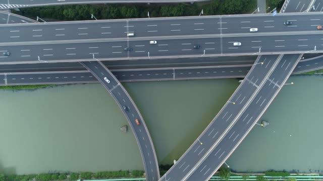 vidéos et rushes de vue aérienne de drone de route multi-niveau de jonction d'autoroute avec des voitures mobiles au coucher du soleil. les voitures se déplacent sur une jonction routière à plusieurs niveaux le concept de l'urbain. ville de suzhou, chine. - route surélevée