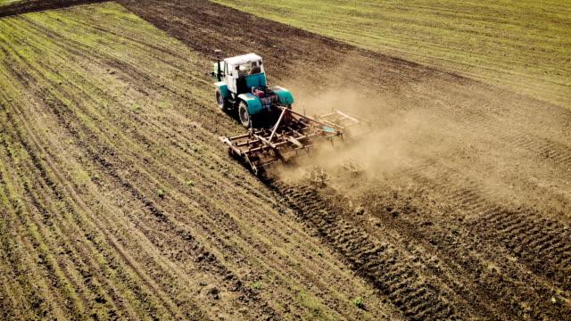 Antenn drönarvy över stora gröna traktor turer på fält och processer jord med jord bearbetning utrustning och rullar video