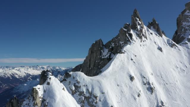 stockvideo's en b-roll-footage met luchtfoto drone uitzicht op mannelijke klimmer stijgende steile besneeuwde berg - sneeuwkap