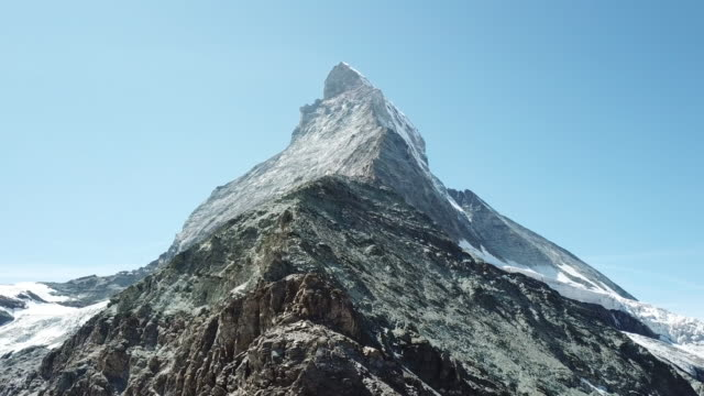 stockvideo's en b-roll-footage met luchtfoto drone uitzicht op de matterhorn berg van onderen op een zonnige dag met blauwe lucht en geen wolken - matterhorn